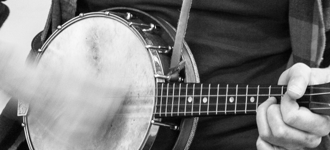 Black and white photo of a man playing the banjo, with his hand blurred from fast movement.