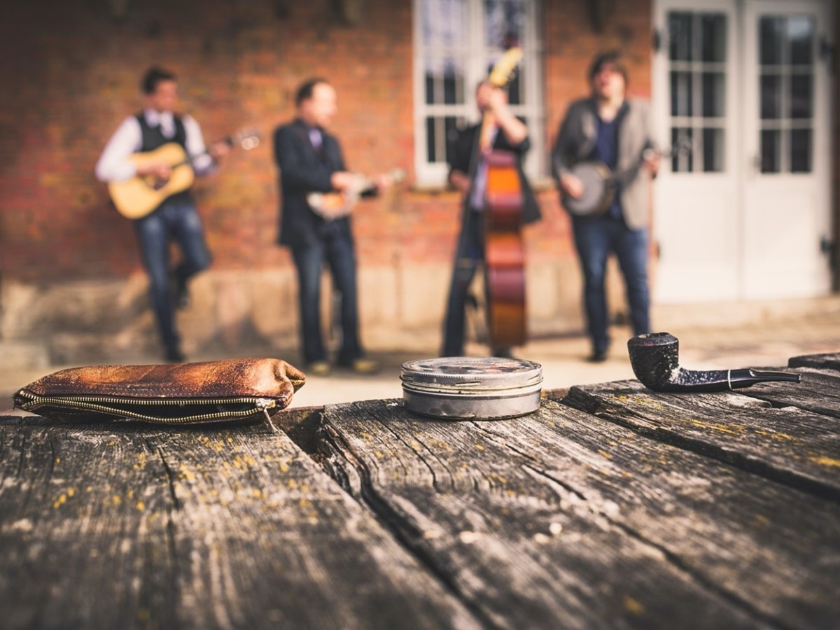 Bluegrass band plays in the background, camera focuses on pipe, wallet, and a small in on a weathered wooden table.