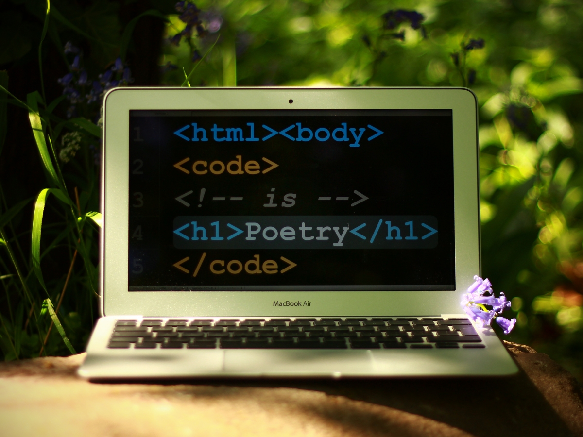 A laptop with html code and the word Poetry on the screen.