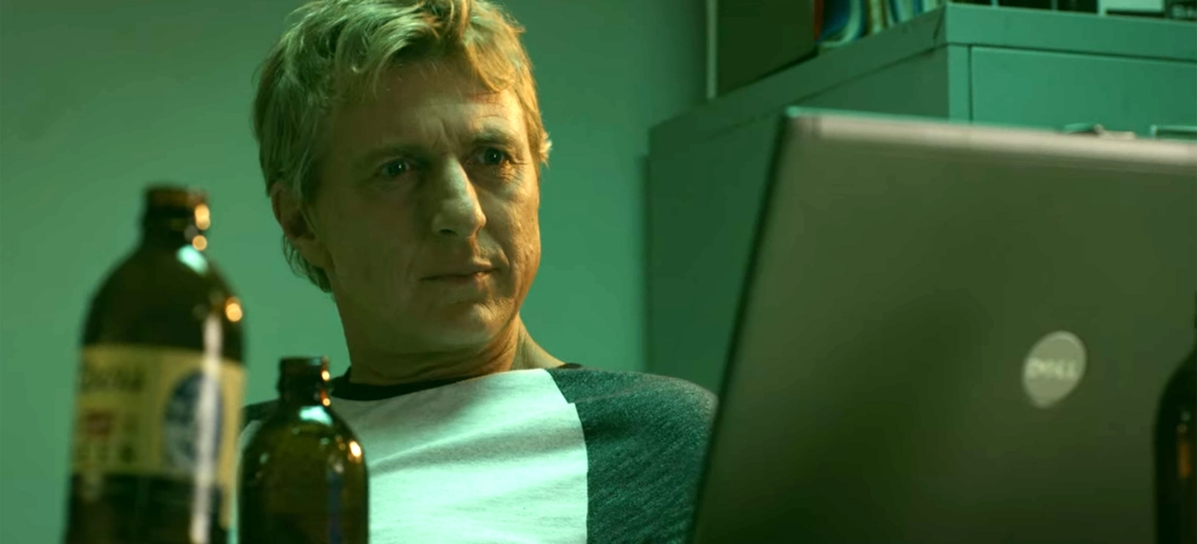 Johnny Lawrence (William Zabka) gives his laptop a puzzled look.