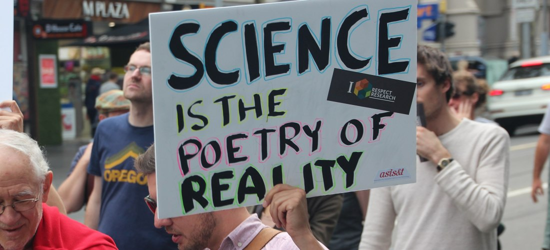 """Protesters holding up a homemade sign saying """"Science is the poetry of reality."""""""